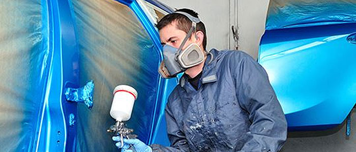 Car being spray painted by a technician